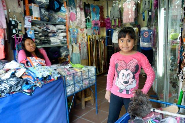 """Sylivia, eine ehemalige Schülerin des Kinderhauses, im Laden ihrer Mutter - Auf dem öffentlichen Markt """"La Cancha"""" sind die Kinder der Verkäuferinnen meist den ganzen Tag sich selbst überlassen oder """"laufen einfach mit"""". Im Kindergarten und der Schule """"Kinderhaus Santa Maria Magdalena Postel"""" werden sie aufgenommen und erhalten eine vorbildliche Erziehung, Cochabamba, Departamento Cochabamba, Bolivien; Foto: Florian Kopp/SMMP"""