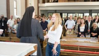 Das Kreuz aus Olivenholz, das Sr. Maria Thoma Dikow überreicht, hat dunkle und helle Streifen. Foto. SMMP/Bock