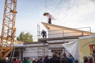 Zimmermeister Michael Hüske befestigt den Richtkranz auf dem Dach der neuen Senioren-WG. (Foto: Beer/SMMP)