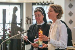 Schwester Ruth steht mit ihrer Professkerze an der Seite der Junioratsleiterin, Schwester Maria Elisabeth Woestmann.