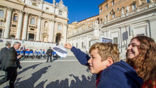An der Seite von Reisebetreuerin Lisa Hochnadel versucht Liam Alexander Janzen die Aufmerksamkeit des Papstes auf sich zu ziehen. Foto: SMMP/Ulrich Bock