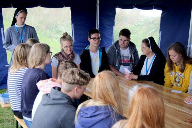 Schwester Lucia Maria diskutiert mit Jugendlichen auf dem Campingplatz bei den Jugendtagen des Bistums Erfurt.