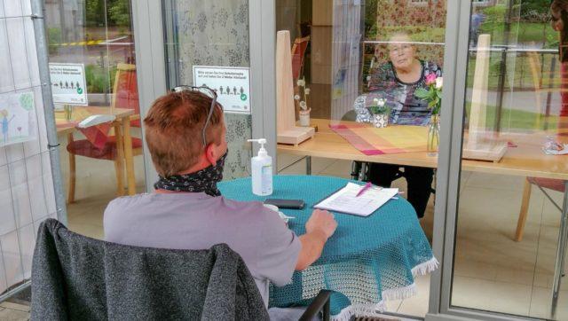 Wiedersehen nach wochenlanger sozialer Distanz: Im Haus St. Josef in Heiden begegnen sich Bewohner und Besucher vor einem bodentiefen Fenster. Foto: SMMP/Irmhild Scheffner